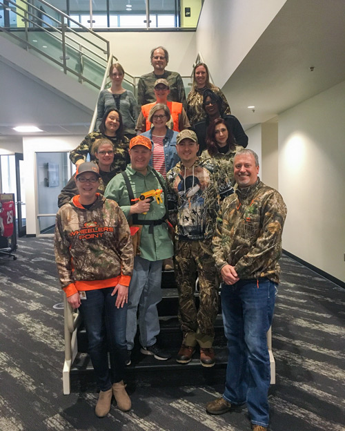 Group of team members dressed in camo for Jeff's birthday
